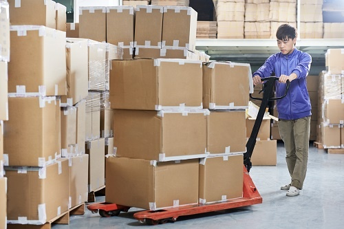 man hauling boxes in a warehouse
